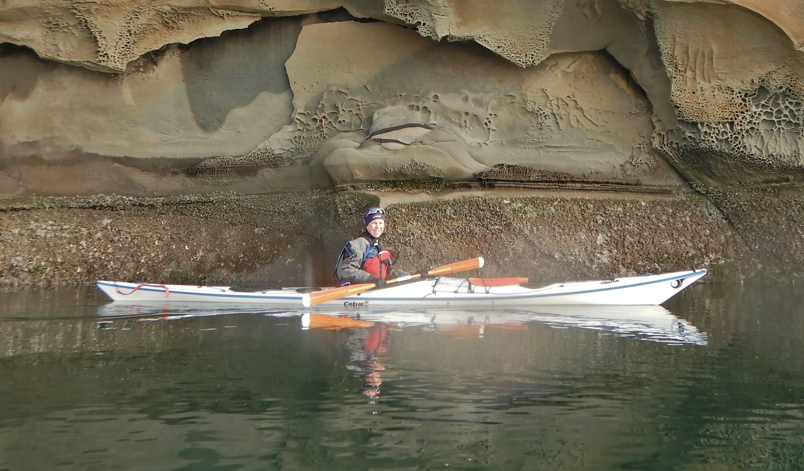 Photo of Caroline Ross in sea kayak at Valdez Cliffs.